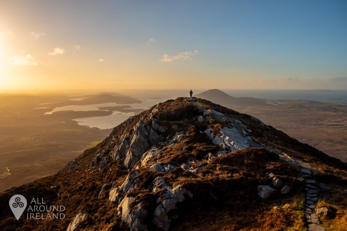 A person photographed in the distance on top of the summit of Diamond Hill in Connemara - National Parks in Ireland