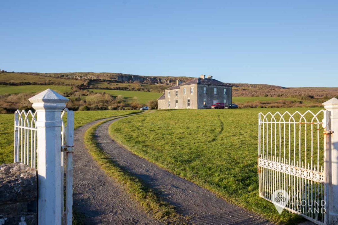 Photo outside the white metal gates of Father Ted'S House in the Burren. A long driveway leads up to the house which was used for the TV show.