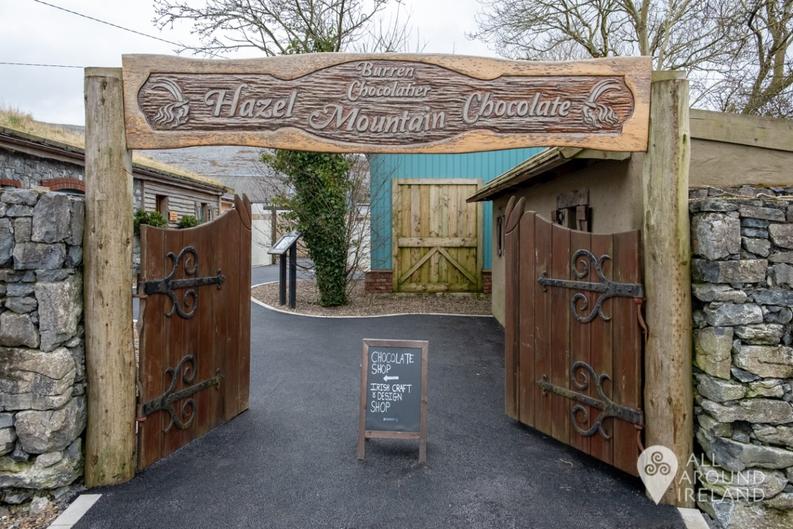 The words Hazel Mountain Chocolate engraved on wood above the gates at the entrance to the factory shop in the Burren
