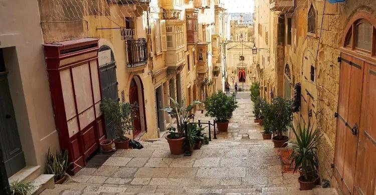 Eine schmale Gasse führt über einige Stiegen durch die Altstadthäuser von Valletta, in Malta. Die Häuser sind aus sandfarbenen Steinen gebaut, links und rechts stehen Blumentöpfe mit grünen Plfanzen.