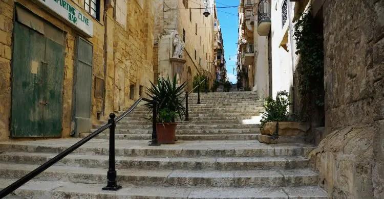 Eine schmale Straße ist von sandfarbenen Steinhäusern eingerahmt.