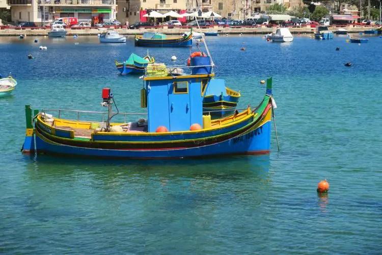 Ein blau-gelb-rotes Luzzu-Boot liegt in der türkislbauen Hafenbucht von Marsaskala vor Anker.