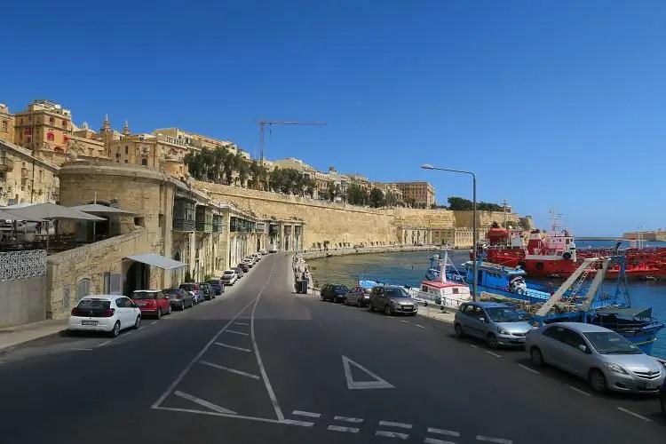 Eine zweispurige Straßen zwischen den Stadtmauern von Valletta und dem Hafen, der direkt am Meer liegt.
