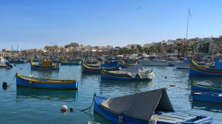 In der Bucht liegen viele kleine Boote vor Anker, dahinter ist die Stadt zu sehen.