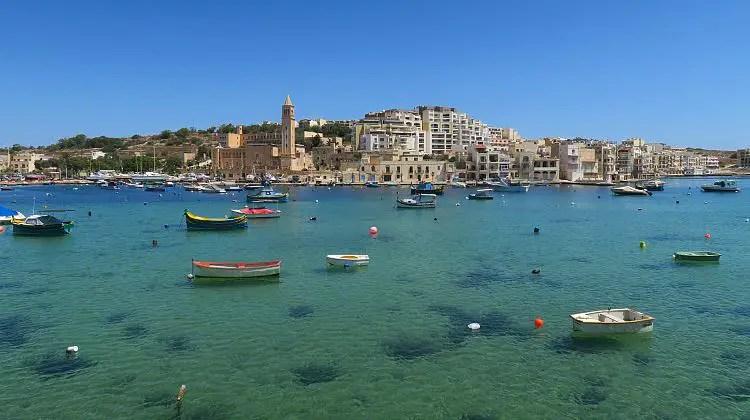 Das flache, kristallklare, türkisblaue Meer im Hafen von Marsaskala mit vielen Luzzu Booten.