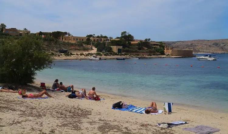 Ein Sandstrand mit Liegestühlen und Badegästen an einer schönen, türkisblauen Bucht mit einer Feriensiedlung im Hintergrund.