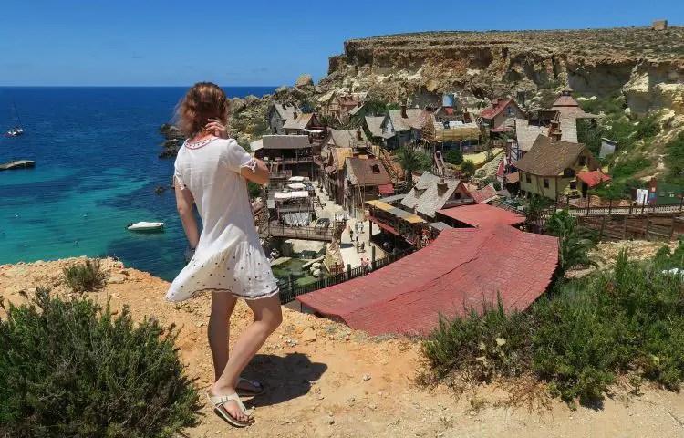 Frau steht oberhalb der Klippen am Popeye Village