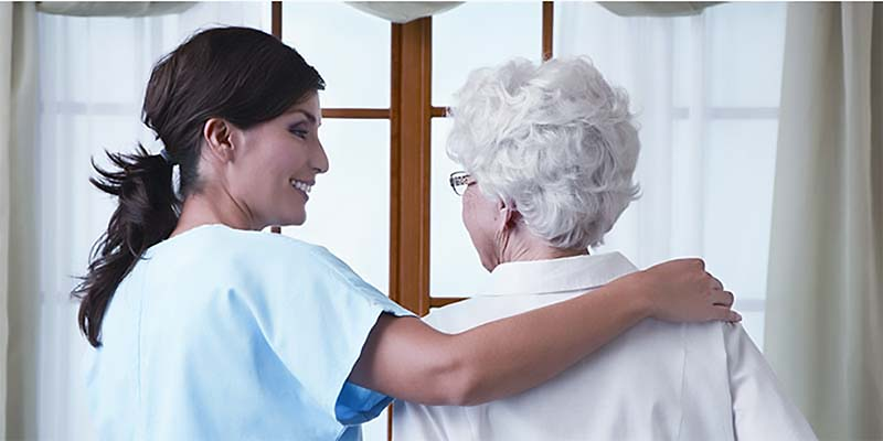 image of caregiver with senior female in wheelchair