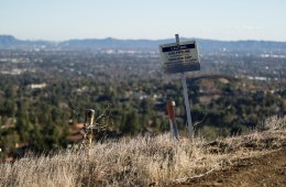Warning signs line the Santa Susana Mountain range near Southern California Gas Company's fenced-off Aliso Canyon facility. A well at the site has been leaking methane since October. Photo: Scott L via Flickr