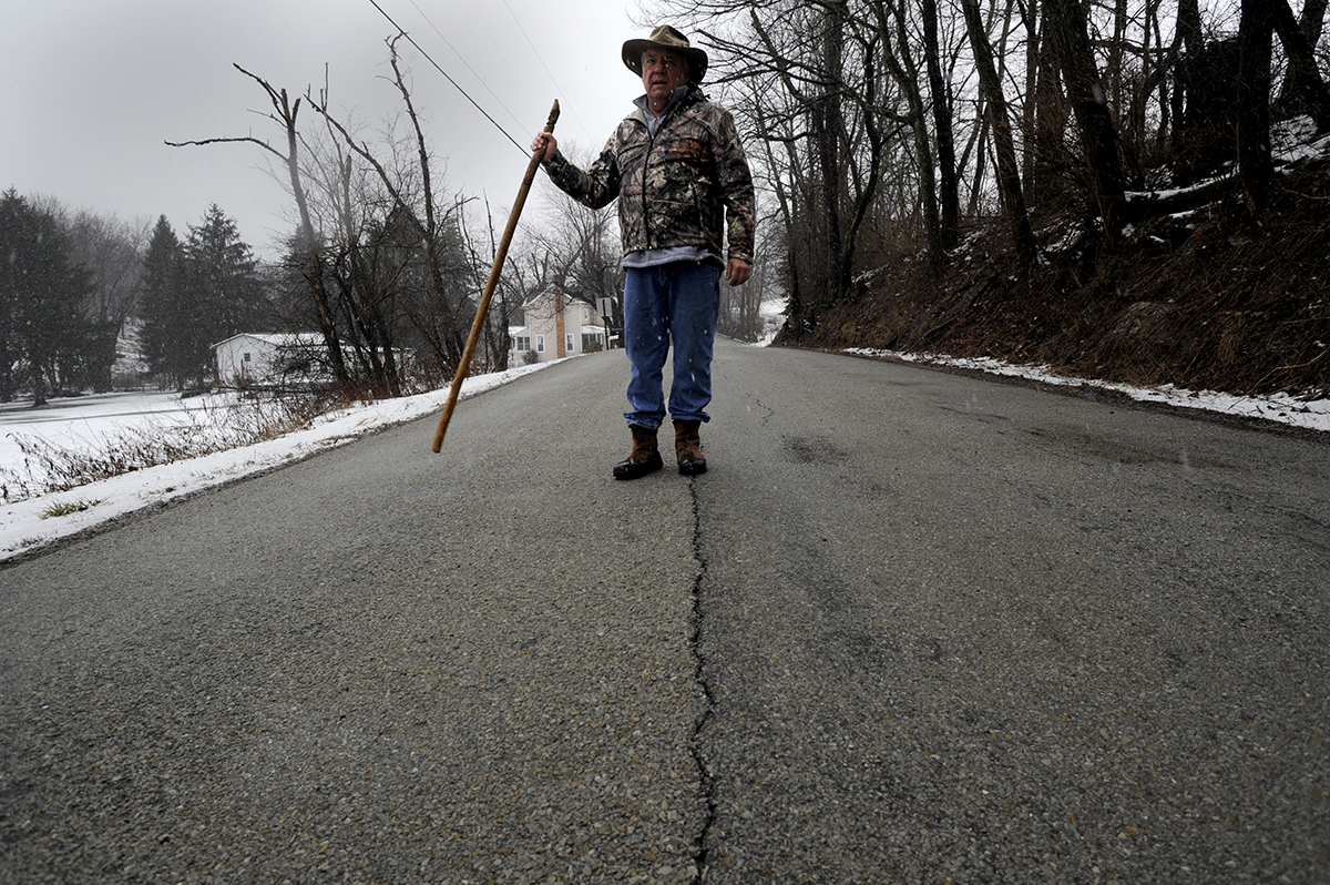 Meyers points out a crack in Dutch Hollow Road near his home. Although the road is rated for 10 tons, Meyers said he worries the road would not be able to support truck traffic that comes with the construction of natural gas wells. Photo : Connor Mulvaney / PublicSource)