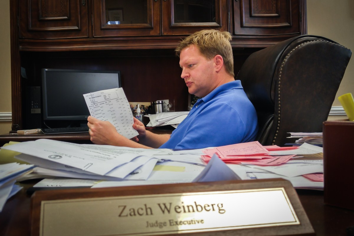 Knott County Judge-Executive Zach Weinberg looks over the tally of property taxes that Jim Justice's company owes Knott County. Photo: Benny Becker / Ohio Valley Resource