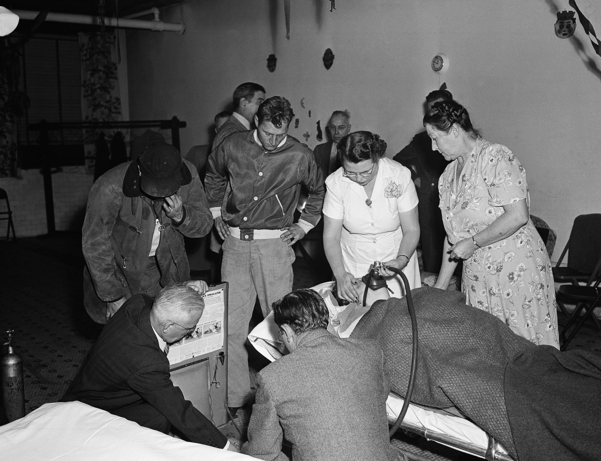 An unidentified nurse administers oxygen to Frieda Van Kirk, 66, October 30, 1948 in Donora, Pennsylvania. She was rushed to the emergency room after being overcome by heavy smog in this town. Unidentified members of her family look on.Photo: AP