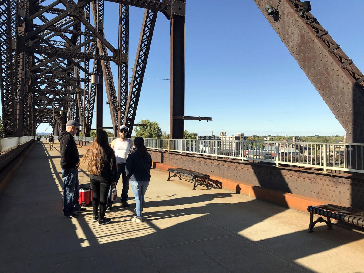 Jason Flickner talks with a group of youth missionaries on the Big Four Bridge over the Ohio River. Photo by Jeff Brooks-Gillies/Environmental Health News
