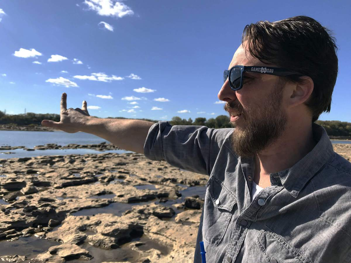 Jason Flickner points out features of the Ohio River from the fossil beds at the Falls of the Ohio State Park. Photo by Jeff Brooks-Gillies/Environmental Health News