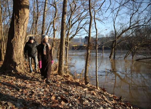 Chuck Keller and Debra Hausrath, both from Fort Thomas, Kentucky, walk along the Licking River Greenway and Trails in Covington, Kentucky, on Dec. 19, 2019. Nearby manufacturer IPSCO Tubulars discharges wastewater containing lead and manganese into the river. (Photo by Leigh Taylor/Eye on Ohio)