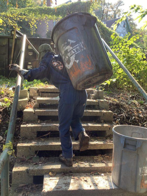 Dani Kramer with trash can on steps