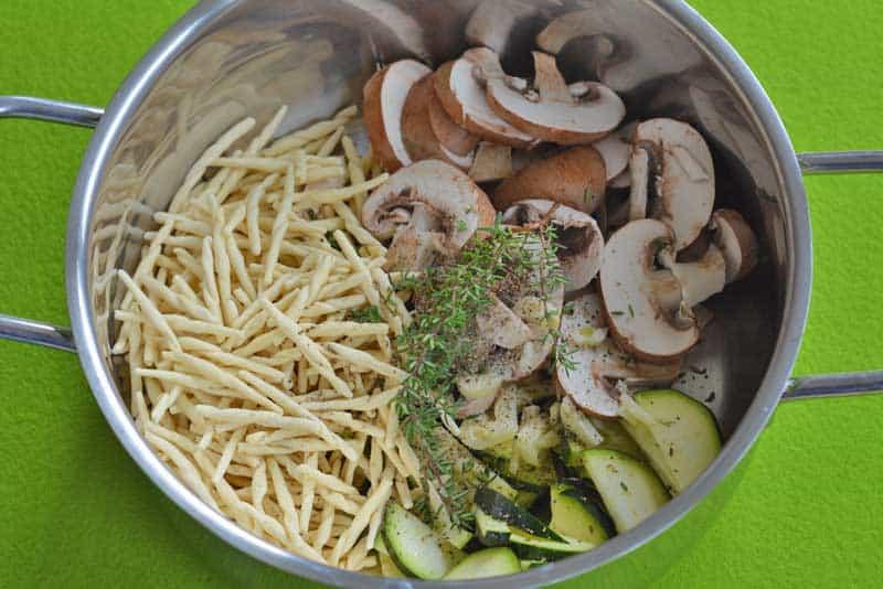 Topf mit Pasta, Champignons, Zucchini und Erbsen