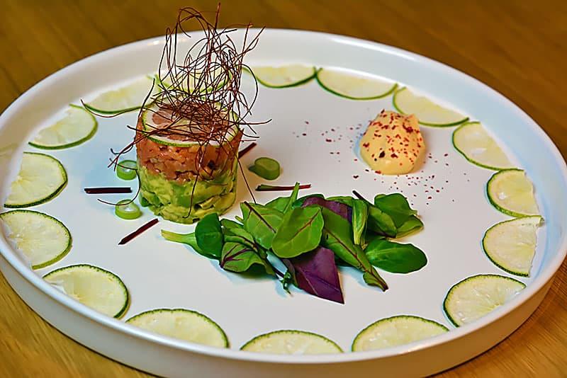 Lachstartar mit Avocado und fruchtiger Frischkäsenocke macht auf einem großen Teller eine gute Figur für jeden Anlass.
