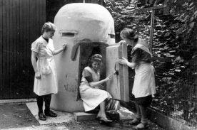 """Drei Mitarbeiterinnen der Wäscherei """"Edelweiß"""" am Dahlweg vor einem kleinen Betonbunker Anfang Juni 1944. (Foto: Stadtarchiv Münster / Kriegschronik Wiemers)"""