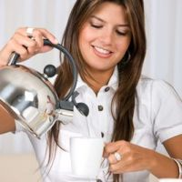 woman pouring boiling water into a coffee cup