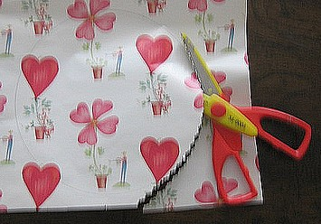 cutting a paper circle with decorative edged scissors