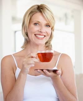 woman drinking clear herb tea