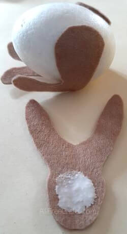 gluing felt bunny pieces onto a foam egg