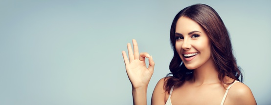 young woman showing okay gesture, with copyspace
