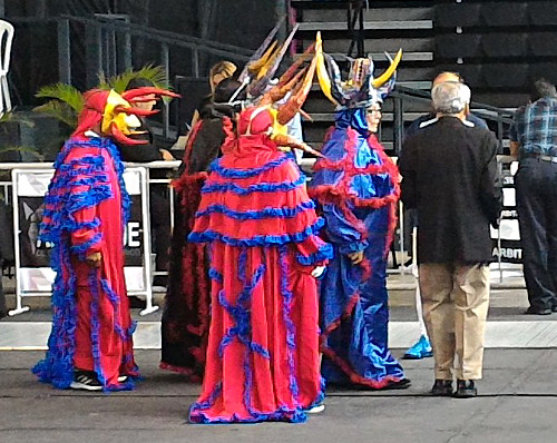 three dancers in brightly colored robes and horned masks in sports stadium