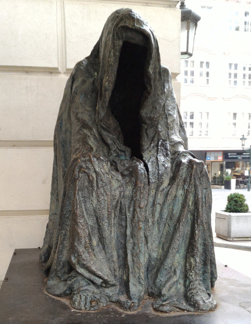 Photo of gunmetal gray statue of an empty hooded cloak