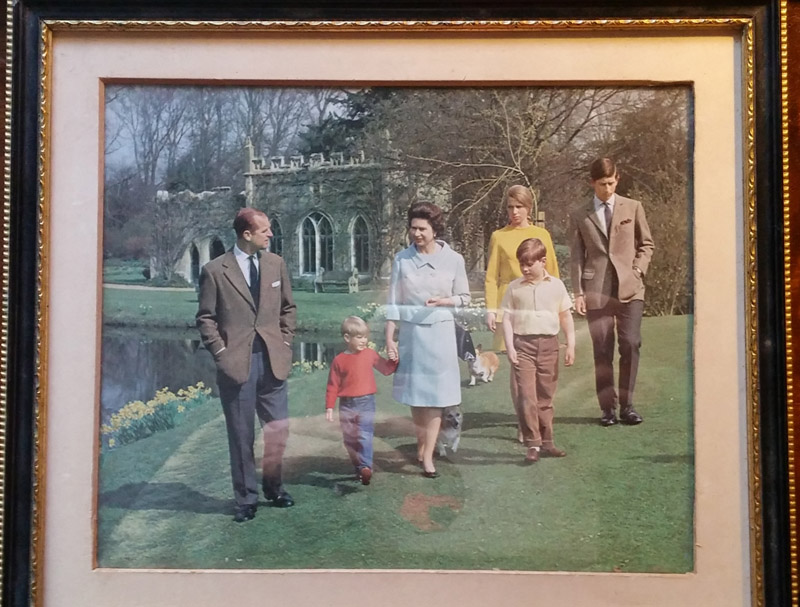 Colour photograph of royal family, behind glass of frame