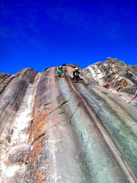 Kids sliding down the rock slide at Saqsaywaman,Cusco, Peru.