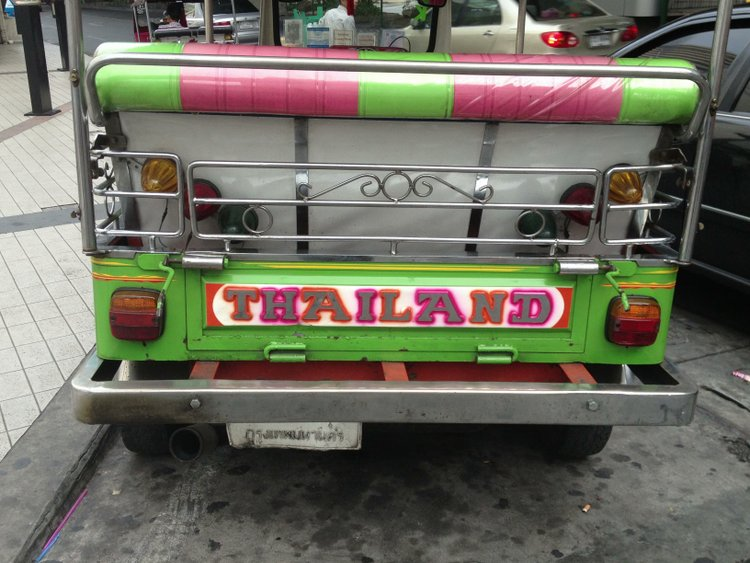 "A pink and green painted tuktuk with the word ""Thailand"""