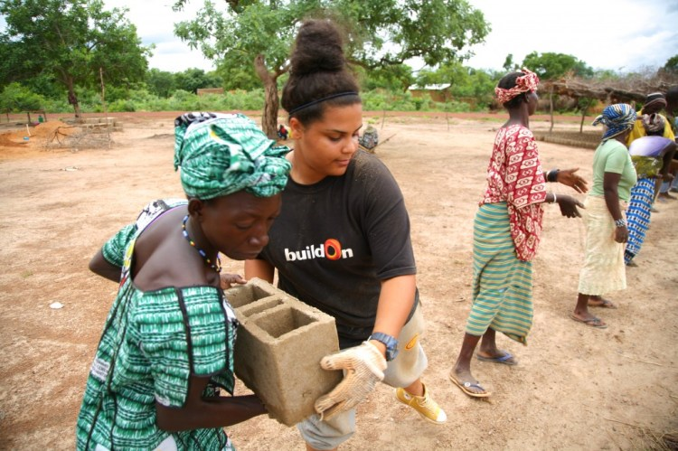A BuildOn volunteer passes a cinderblock to a local woman during construction of a school in Africa