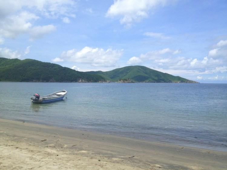A beautiful beach and a fishing boat at Parque Tayrona