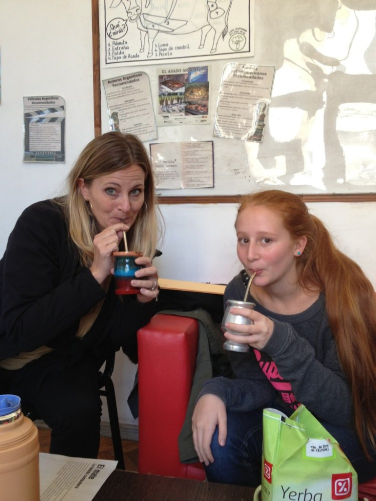 A mom and daughter sip mate through  a bombilla.