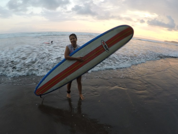 R poses with the board and ocean.