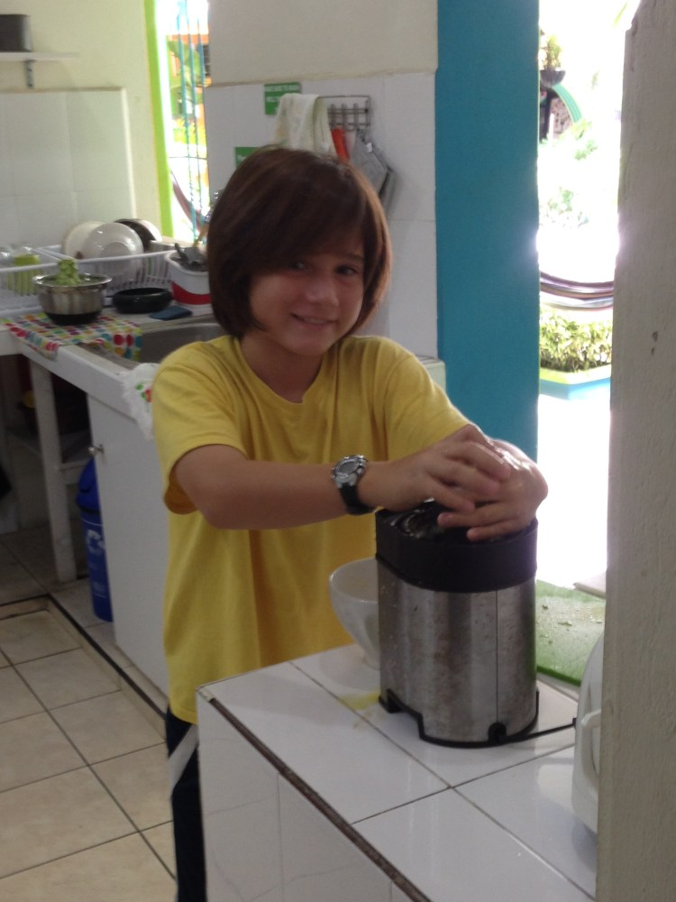 J juices some oranges in the kitchen at Casa Verde in Santa Ana, El Salvador