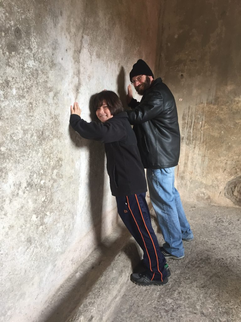 The author and his son try out the public urinal on a Pompeii tour for kids.