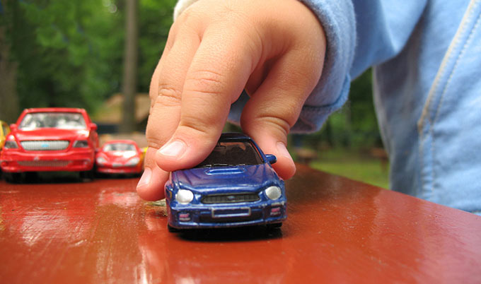 A kid's hand moving a toy car.