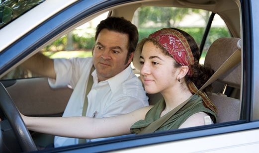 A father teaching his teenage daughter how to drive.