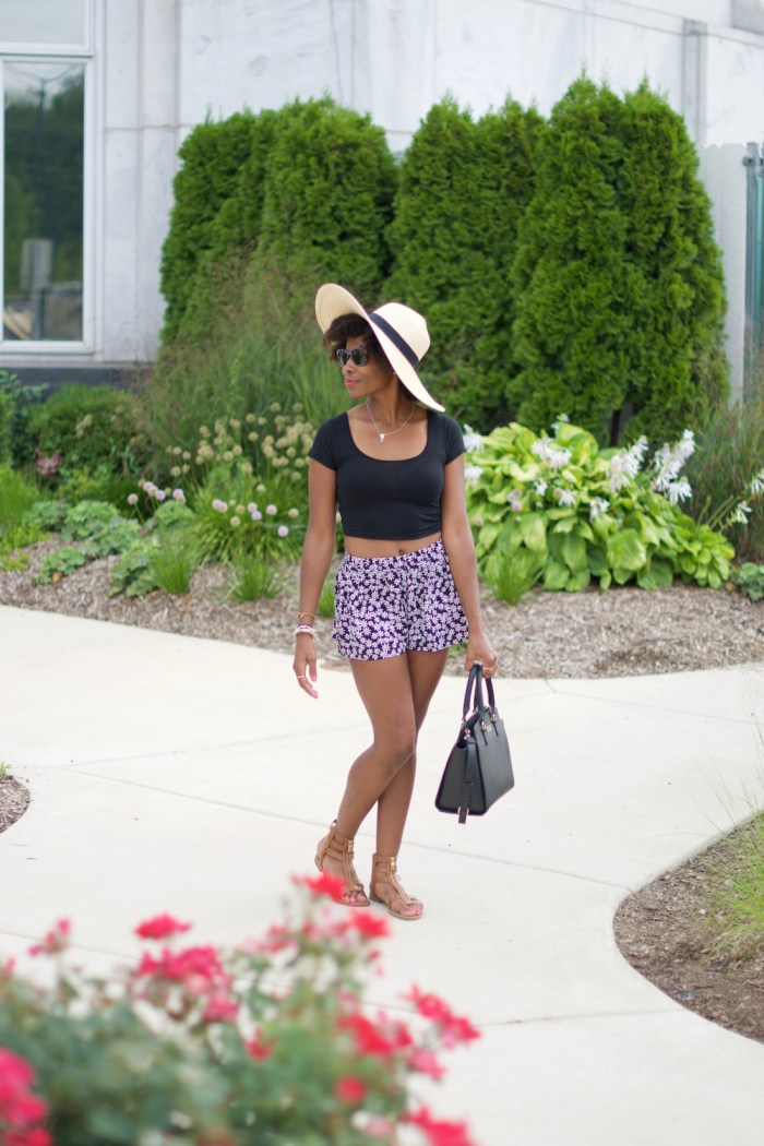 Casual style: straw hat, cropped tee and daisy print high-waist shorts...