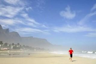 Atleta na praia de Camps Bay por entre uma bruma matinal
