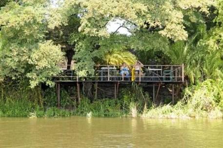 Turistas junto a um resort nas margens do Okavango