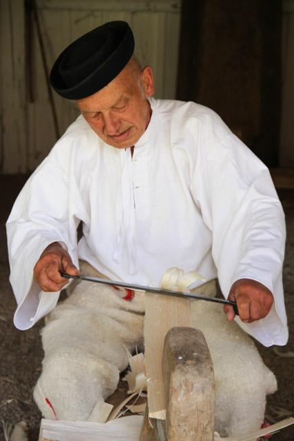 Slovak man peels a piece of wood as he makes a roof shingle