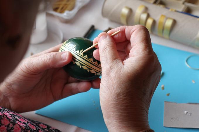 Gluing straw onto a Slovak Easter egg