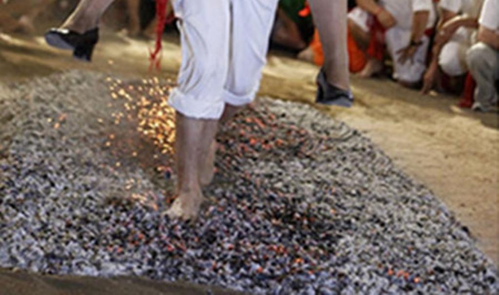 Das Tragen des Bräutigams die Braut auf Kohle zu Fuß