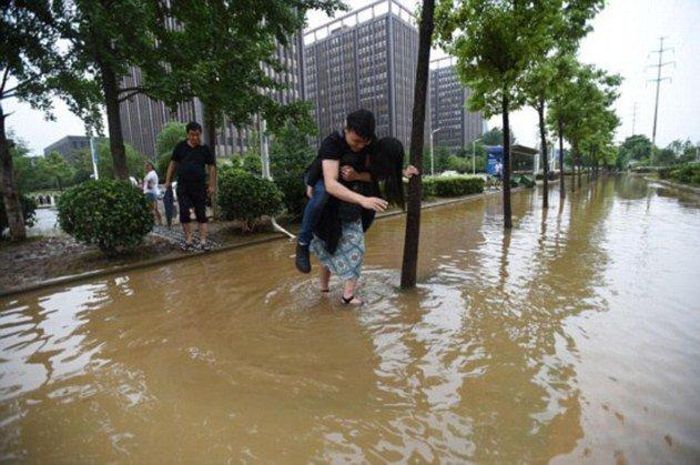 صينية تحمل خطيبها على ظهرها لعبور مياه الفيضان