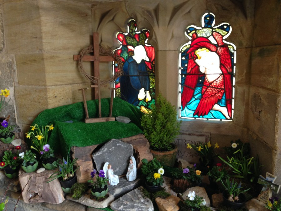 An image of a garden tomb made with rocks and greenery in the church porch