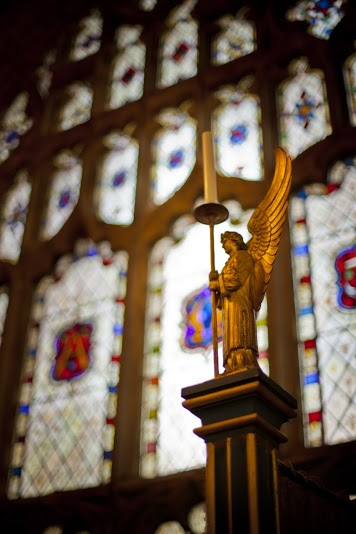 Image of an angel with a candle, in front of stained glass in St Michael's Church